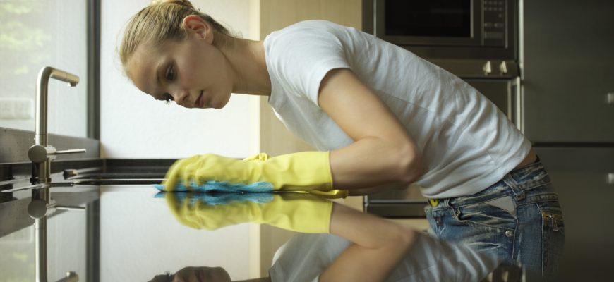 Девушка моет поверхность на кухне