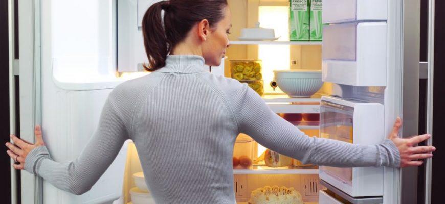 Девушка открыла дверцы холодильника