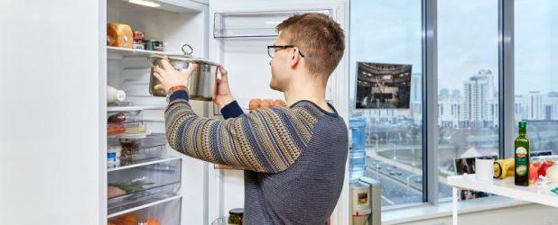 Мужчина ставит кастрюлю в холодильника