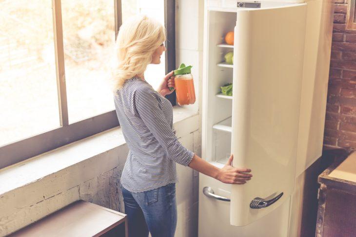 Девушка рядом с холодильником