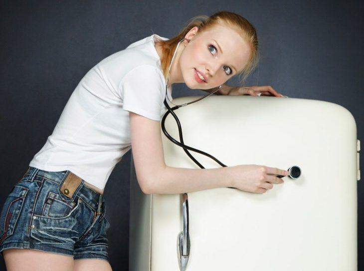 Девушка прикладывает к холодильнику стетоскоп