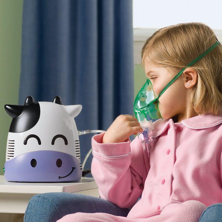 Девочка дышит детским небулайзером